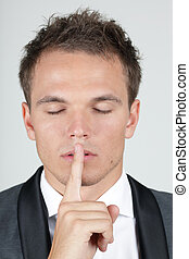 Portrait of businessman showing silence gesture with his...