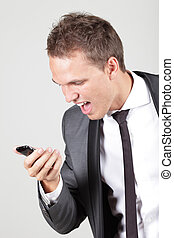 Profile view of a young business man screaming in his...