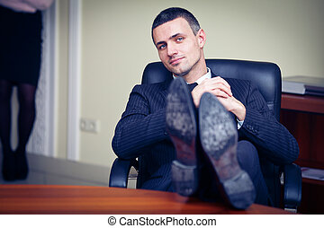 businessman relaxing at the office with his shoes on the...