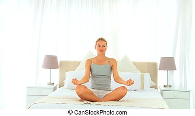 Blonde woman doing the lotus position on her bed