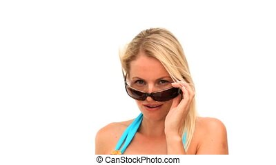 Attractive blonde woman removing her sunglasses against a...