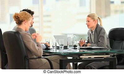 Threesome of business people at a desk