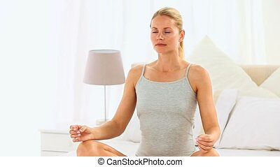 Blonde woman doing yoga position on her bed