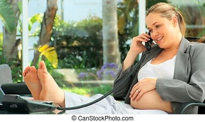 Relaxed pregnant woman speaking on the phone at her desk
