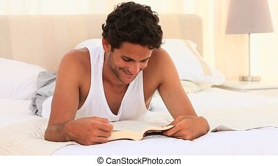 Man in pyjamas reading a book on his bed