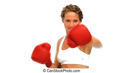 Dynamic blonde woman with boxing gloves isolated on a white...