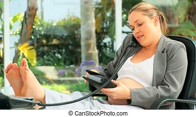 Pregnant business woman on the phone at her desk