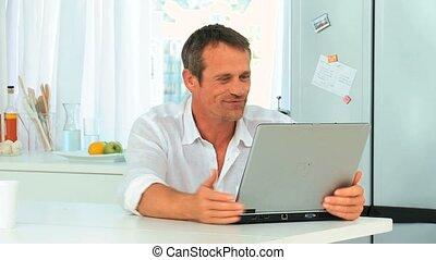 Casual man laughing in front of his laptop in the kitchen