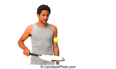 Handsome man playing tennis against a white background