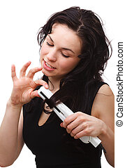 Woman is using hair straightener - Young woman is using hair...