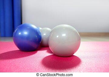 pilates toning balls over red yoga mat