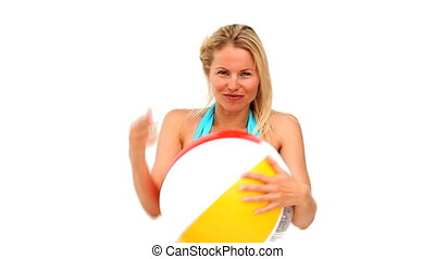 Cute woman playing with a beach ball in swimsuit