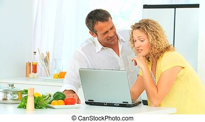 Lovely couple looking at a recipe on internet in their...