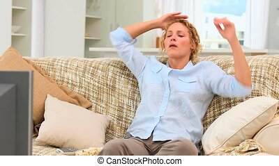 Curly haired woman watching sports on the tv in her living...