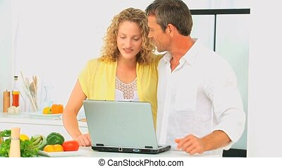 Casual couple looking at a recipe on a laptop in the kitchen