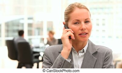 Blonde business woman speaking on the phone in an office