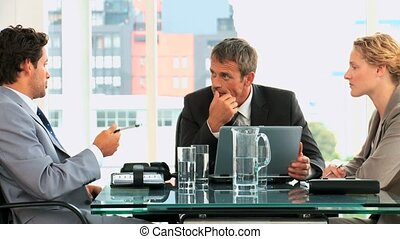 Threesome of business people speaking to each others