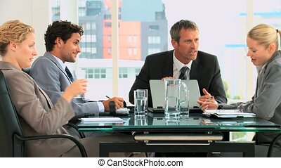 Four business people speakingto each others in an office