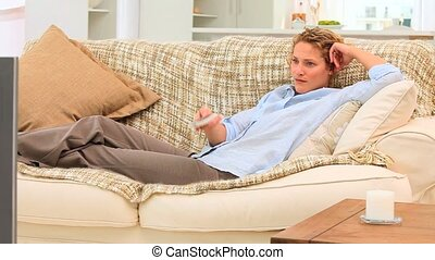 Curly haired woman watching the tv - Curly blonde woman...