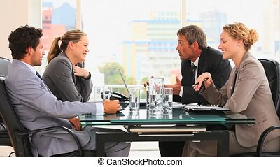 Four business people talking during a meeting at an office