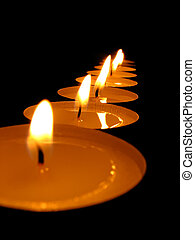 candles  - Some burning candles on a black background.
