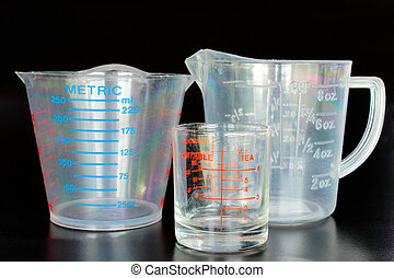 Measuring cups on the black background.