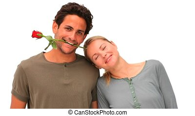Handsome man with rose between his teeth next to his wife