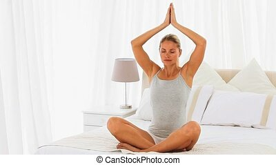 Woman doing the lotus position in pyjamas on her bed