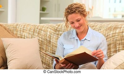 Curly-haired woman looking at an album on her sofa