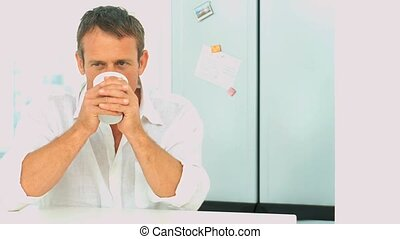 Male drinking a cup of coffee durung the morning in his...