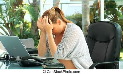 Very tired pregnant woman at an office touching her back