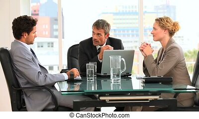 Three business people talking to each others in an office
