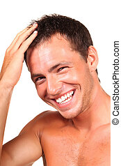 Closeup of a happy young man looking at camera and touching...