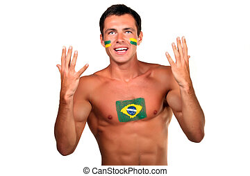 Portrait of a brazilian football fan with flag on his body...