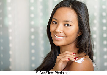 Portrait of a beautiful asian woman putting cream on her shoulder