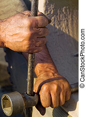 the hands of men working with a lever