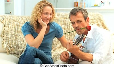 Casual playing guitar next to his wife with a rose between...