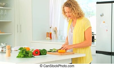 Curly haired woman preparing the lunch in the kitchen