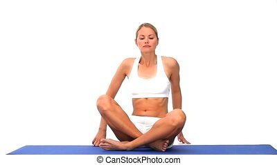 Blonde lady meditating on a blue ground cloth