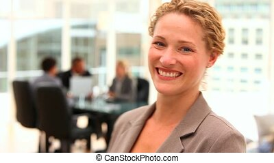 Curly haired business woman looking at the camera during a...