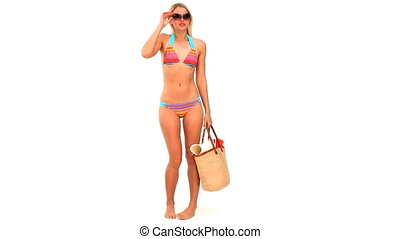Blonde woman in swimsuit with a bag isolated on a white...