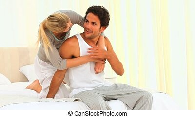 Woman giving her boyfriend a cuddle on their bed