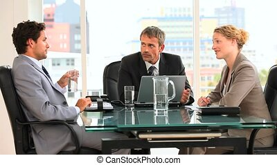 Threesome of business people during a meeting at a desk