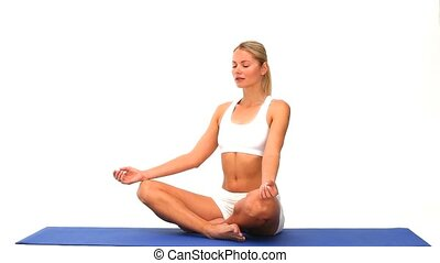 Cute woman meditating on a blue ground cloth