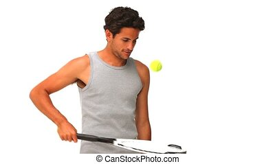 Dark-haired man with a racket and tennis ball isolated on a...