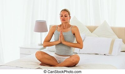 Lovely woman doing the lotus position on her bed