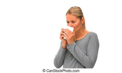 Blonde woman drinking a cup of coffee against a white...