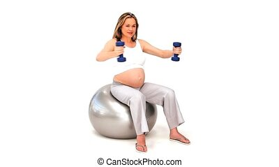Expecting woman on a gym ball with dumbbells