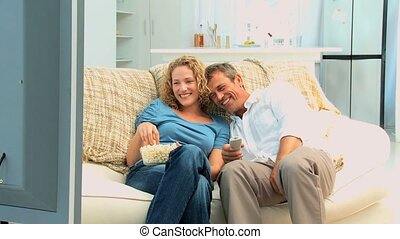 Lovely couple laughing in front of the tv in the living room
