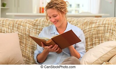 Curly haired woman looking at an album in her living room